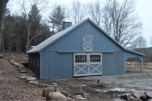 Completed blue modular barn with lean to